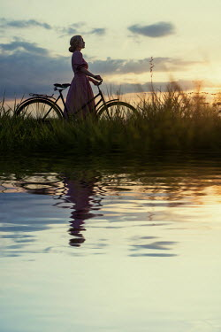 Magdalena Russocka retro woman with bike standing by river at sunset