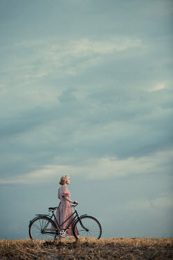 Magdalena Russocka retro woman in gingham dress with bike walking in field