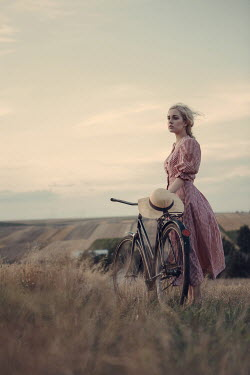 Magdalena Russocka retro woman with bike standing in field