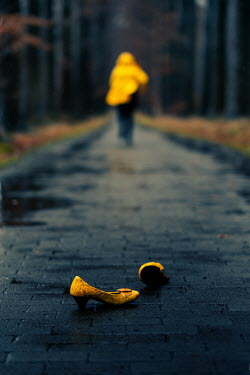 Maria Petkova running woman in yellow coat and abandoned yellow shoes
