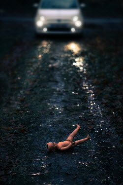 Maria Petkova car with headlights and doll on road at night