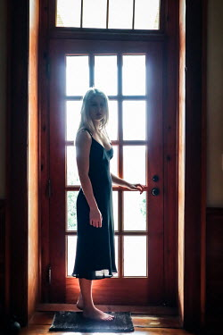 Stephen Carroll Young woman in black dress standing at door