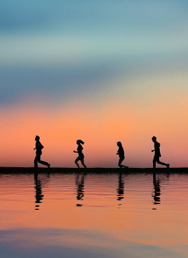 Elisabeth Ansley Silhouette of friends running by lake at sunset