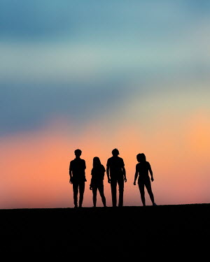 Elisabeth Ansley Silhouette of friends standing side by side at sunset