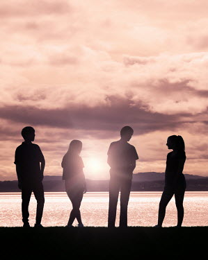 Elisabeth Ansley Silhouette of friends standing by lake at sunset