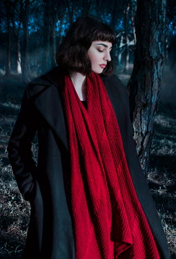Giada Piras Young woman in black coat and red scarf in forest