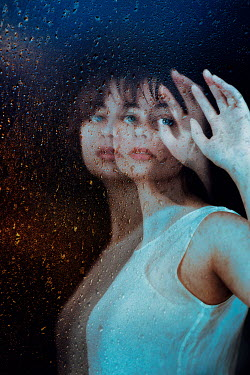 Giada Piras Double exposure of young woman with hand raised behind wet window