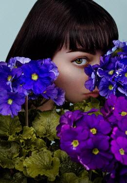 Giada Piras Woman hiding behind purple flowers