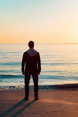 Giada Piras Young man standing on beach at sunset