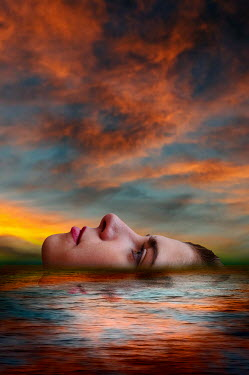Valentino Sani Young woman in floating in lake at sunset