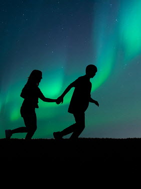 Elisabeth Ansley Silhouette of teenage couple holding hands and running under northern lights