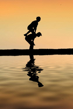 Elisabeth Ansley Silhouette of boys playing leapfrog by lake at sunset
