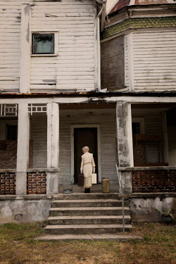 Erika Masterson Girl in white dress holding suitcases on porch of weathered house