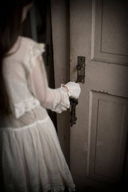 Erika Masterson Girl in white dress opening door with key