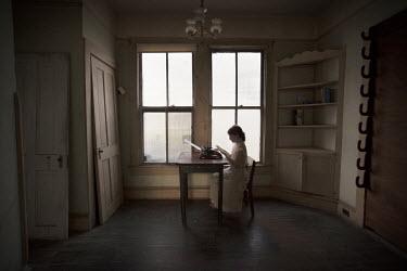 Erika Masterson Girl in white dress using typewriter by window