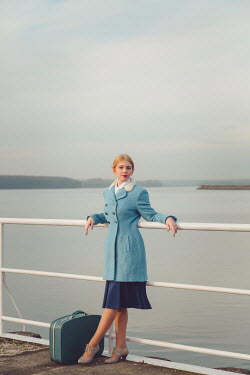 Joanna Czogala Young woman in vintage blue coat at railing by sea Women