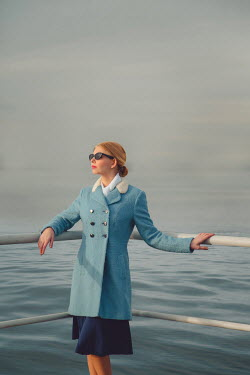 Joanna Czogala Young woman in vintage blue coat and sunglasses at railing by sea Women