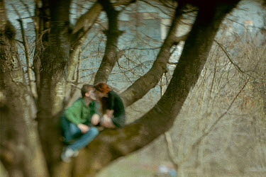 Dmitriy Bilous Teenage couple kissing in tree
