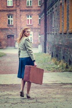 Joanna Czogala Young woman in vintage jacket with suitcase