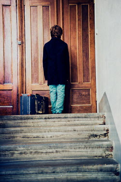 Katya Evdokimova Boy in black coat waiting at door with suitcase
