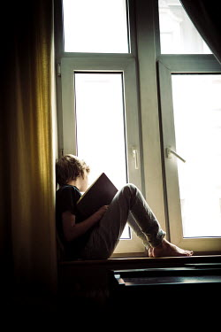 Katya Evdokimova Boy reading on windowsill