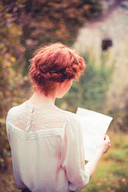 Marie Carr Young woman with braided red hair reading letter