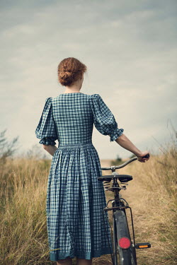 Magdalena Russocka woman with bike standing in countryside