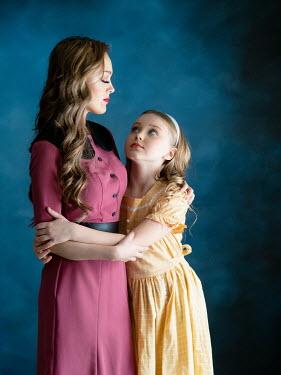Elisabeth Ansley Woman in vintage dress hugging her daughter