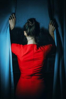 Ildiko Neer Woman in red dress between curtains