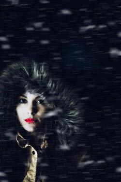 Ildiko Neer Young woman with fur hood in snowstorm