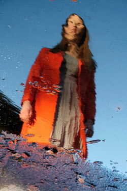 Ute Klaphake Reflection of young woman in red coat in puddle