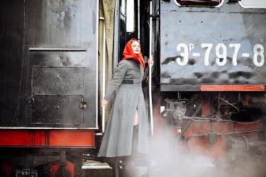 Marta Syrko Young woman in vintage headscarf on train