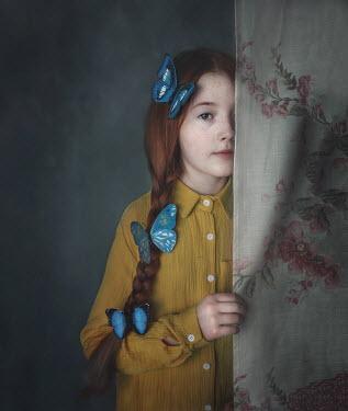Anna Buczek Girl with blue butterflies in hair hiding behind curtain