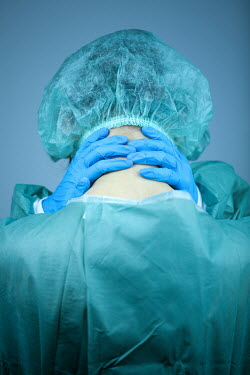 Magdalena Russocka Tired female surgeon massaging her neck