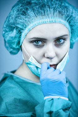 Magdalena Russocka Female surgeon taking off surgical mask