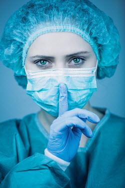 Magdalena Russocka Female surgeon making hush gesture