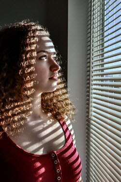 Stephen Carroll Young woman by window with blinds