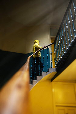 Natasza Fiedotjew Man in yellow rain coat walking up stairs