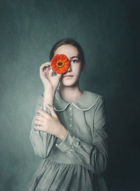 Anna Buczek Teenage girl holding orange flower over eye