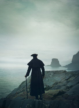 Mark Owen Pirate with hat, coat, and cane on cliff by sea