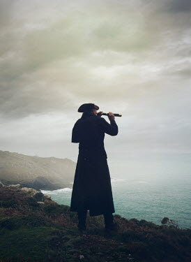 Mark Owen Pirate in hat and coat using telescope by sea
