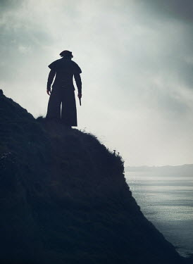 Mark Owen Pirate in hat and coat with pistol on hill by sea