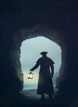 Mark Owen Pirate in hat and coat with lantern in cave