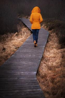 Maria Petkova Woman in yellow jacket walking on boardwalk