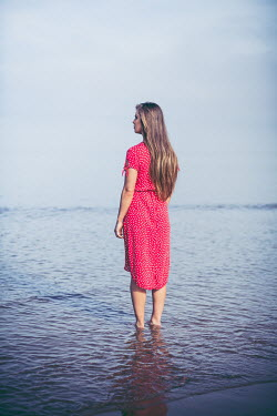Marie Carr Young woman in red dress standing in water at beach