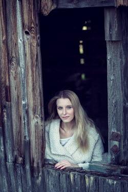 Carmen Spitznagel Young woman in woollen coat in window of wooden shed