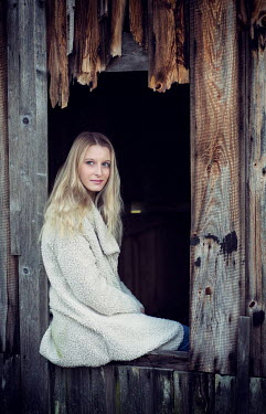 Carmen Spitznagel Young woman in woollen coat sitting in window of wooden shed