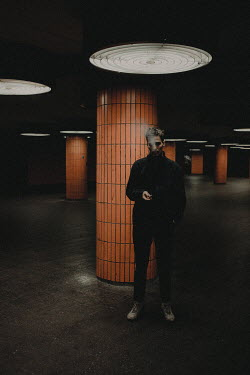 Elisabeth Mochner Young man smoking by orange pillar in parking garage