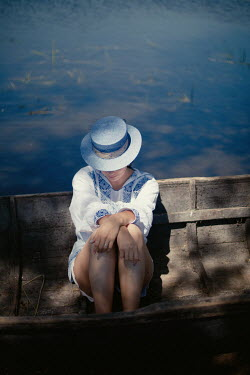 Felicia Simion Young woman in straw hat and dress sitting in rowboat