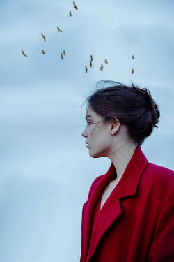 Natasza Fiedotjew Young woman in red coat with birds above her head